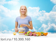 Купить «smiling woman squeezing fruit juice over sky», фото № 10300160, снято 26 апреля 2015 г. (c) Syda Productions / Фотобанк Лори