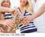 Купить «close up of friends clinking bottles with drinks», фото № 10300340, снято 13 июля 2014 г. (c) Syda Productions / Фотобанк Лори