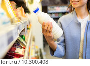 Купить «happy woman holding milk bottle in market», фото № 10300408, снято 20 декабря 2014 г. (c) Syda Productions / Фотобанк Лори