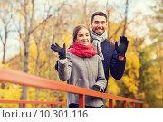 Купить «smiling couple hugging on bridge in autumn park», фото № 10301116, снято 18 октября 2014 г. (c) Syda Productions / Фотобанк Лори