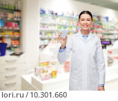 woman pharmacist with pills drugstore or pharmacy. Стоковое фото, фотограф Syda Productions / Фотобанк Лори