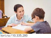 Купить «Teacher helping a little boy during class», фото № 10335280, снято 7 июля 2015 г. (c) Wavebreak Media / Фотобанк Лори