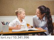 Купить «Teacher helping a student in class», фото № 10341996, снято 7 июля 2015 г. (c) Wavebreak Media / Фотобанк Лори