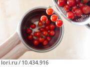 Купить «Cherry Tomatoes Tumbling From Metal Colander Into Metal Pan», фото № 10434916, снято 21 мая 2019 г. (c) PantherMedia / Фотобанк Лори