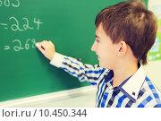 little smiling schoolboy writing on chalk board. Стоковое фото, фотограф Syda Productions / Фотобанк Лори