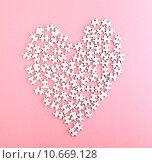 Купить «Puzzle made heart shape on pink background », фото № 10669128, снято 10 декабря 2018 г. (c) PantherMedia / Фотобанк Лори