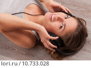 Купить «Beautiful woman with headphones lying on the floor», фото № 10733028, снято 23 марта 2019 г. (c) PantherMedia / Фотобанк Лори