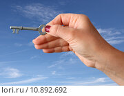Hand holding a key over sky background. Стоковое фото, фотограф Philip Lange / PantherMedia / Фотобанк Лори