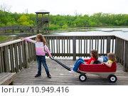 Купить «girls looking at park lake with outdoor dump cart», фото № 10949416, снято 18 октября 2018 г. (c) PantherMedia / Фотобанк Лори