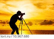 Купить «Silhouette of photographer with tripot at sunset», фото № 10967680, снято 20 сентября 2018 г. (c) PantherMedia / Фотобанк Лори