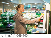 Купить «Pretty, young woman shopping for fruits and vegetables in produce department of a grocery store/supermarket», фото № 11049440, снято 19 июня 2019 г. (c) PantherMedia / Фотобанк Лори