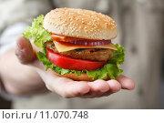 Купить «Гамбургер в мужской ладони», фото № 11070748, снято 21 августа 2015 г. (c) Лидия Рыженко / Фотобанк Лори