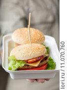 Купить «Контейнер с двумя бургерами в мужской ладони», фото № 11070760, снято 21 августа 2015 г. (c) Лидия Рыженко / Фотобанк Лори
