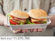 Купить «Контейнер с двумя бургерами в мужских ладонях», фото № 11070780, снято 21 августа 2015 г. (c) Лидия Рыженко / Фотобанк Лори