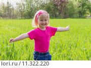 Маленькая девочка играет на траве возле леса. Стоковое фото, фотограф Вячеслав Волков / Фотобанк Лори