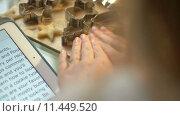 Купить «Woman reads recipe and makes molds for pastry dough», видеоролик № 11449520, снято 25 августа 2015 г. (c) Данил Руденко / Фотобанк Лори