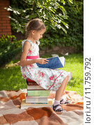 Купить «girl in cute dress sitting on pile of books and reading», фото № 11759792, снято 15 октября 2019 г. (c) PantherMedia / Фотобанк Лори