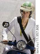 Купить «Woman in crash helmet riding on scooter in street, smiling, front view, close-up (tilt)», фото № 11957808, снято 18 октября 2019 г. (c) PantherMedia / Фотобанк Лори