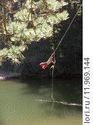 Купить «Boy (9-11), in swimming shorts, swinging on rope above lake», фото № 11969144, снято 17 октября 2018 г. (c) PantherMedia / Фотобанк Лори