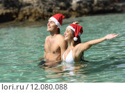 Купить «Couple bathing on the beach on christmas holidays», фото № 12080088, снято 23 февраля 2019 г. (c) PantherMedia / Фотобанк Лори