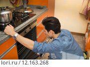 Купить «Young man checking food he baked in oven», фото № 12163268, снято 23 октября 2018 г. (c) PantherMedia / Фотобанк Лори