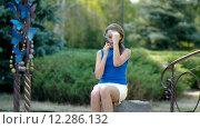 Девушка-подросток говорит по телефону в парке. Стоковое видео, видеограф Ivan Dubenko / Фотобанк Лори