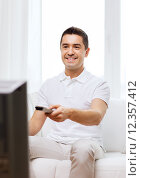 Купить «smiling man with remote control watching tv», фото № 12357412, снято 29 января 2015 г. (c) Syda Productions / Фотобанк Лори