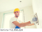 Купить «builder with grinding tool indoors», фото № 12358224, снято 25 сентября 2014 г. (c) Syda Productions / Фотобанк Лори