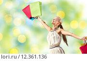 Купить «smiling woman with shopping bag rising hands», фото № 12361136, снято 19 июня 2013 г. (c) Syda Productions / Фотобанк Лори