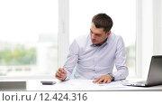 Купить «busy businessman with laptop and papers in office», видеоролик № 12424316, снято 9 июля 2015 г. (c) Syda Productions / Фотобанк Лори