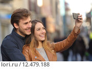 Купить «Couple taking selfie photo with a smart phone in the street», фото № 12479188, снято 18 февраля 2019 г. (c) PantherMedia / Фотобанк Лори