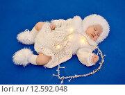 Купить «Спящий младенец  в новогоднем костюме Снежинки со светящейся гирляндой в форме сердца на синем фоне», фото № 12592048, снято 16 декабря 2014 г. (c) Ирина Борсученко / Фотобанк Лори