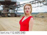 Купить «Азиатская девушка в красном платье на фоне карьерного экскаватора», фото № 12605040, снято 29 августа 2015 г. (c) Сосенушкин Дмитрий Александрович / Фотобанк Лори