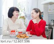 Купить «Две пожилые женщина сидят за столом с чашками, чайником и оладьями. Подруги смотрят друг на друга на кухне», фото № 12607596, снято 11 февраля 2015 г. (c) Дарья Филимонова / Фотобанк Лори