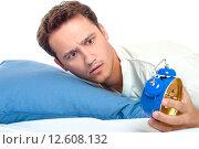 Мужчина проспал, смотрит удивленно на будильник. Стоковое фото, фотограф Евгений Пидеркин / Фотобанк Лори