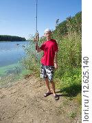 Купить «Молодой рыбак с пойманной щукой на озере Селигер, Тверская область», эксклюзивное фото № 12625140, снято 21 августа 2015 г. (c) Елена Коромыслова / Фотобанк Лори