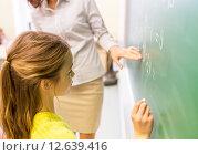 schoolgirl and teacher writing on chalk board. Стоковое фото, фотограф Syda Productions / Фотобанк Лори