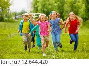 Купить «Счастливая маленькая девочка с друзьями запускает авиамодель летом», фото № 12644420, снято 31 мая 2015 г. (c) Сергей Новиков / Фотобанк Лори