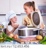 Купить «Mother and child preparing meat», фото № 12653456, снято 16 ноября 2019 г. (c) Яков Филимонов / Фотобанк Лори