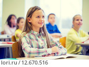 group of school kids with notebooks in classroom. Стоковое фото, фотограф Syda Productions / Фотобанк Лори