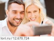 Купить «happy couple taking selfie with smartphone», фото № 12670724, снято 15 июля 2015 г. (c) Syda Productions / Фотобанк Лори