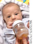 Купить «Маленький ребенок пьет из бутылочки», фото № 12672796, снято 22 мая 2014 г. (c) Виктор Топорков / Фотобанк Лори