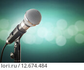 Купить «Microphone on the green abstract background.», фото № 12674484, снято 23 мая 2019 г. (c) Maksym Yemelyanov / Фотобанк Лори