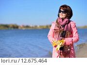Молодая женщина в пальто на берегу реки с осенними листьями. Стоковое фото, фотограф Станислав Самойлик / Фотобанк Лори