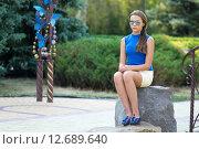Девушка в очках сидит на камне в парке. Стоковое фото, фотограф Ivan Dubenko / Фотобанк Лори