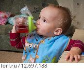 Купить «Мальчик (1 год и 3 месяца) пьет из бутылочки», эксклюзивное фото № 12697188, снято 7 сентября 2015 г. (c) Вячеслав Палес / Фотобанк Лори