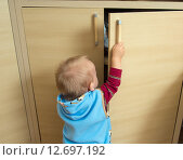 Купить «Мальчик (1 год и 3 месяца) открывает шкаф», фото № 12697192, снято 7 сентября 2015 г. (c) Вячеслав Палес / Фотобанк Лори