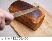 Купить «Резка чёрного Дарницкого хлеба на разделочной доске», фото № 12706460, снято 13 сентября 2015 г. (c) Алёшина Оксана / Фотобанк Лори