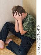 Купить «Boy teenager with depression sitting in the corner of room», фото № 12716416, снято 20 сентября 2015 г. (c) Володина Ольга / Фотобанк Лори