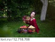 Красивая молодая женщина сидит на траве в осеннем саду с урожаем фруктов и ягод (2015 год). Стоковое фото, фотограф Андрей Шарашкин / Фотобанк Лори
